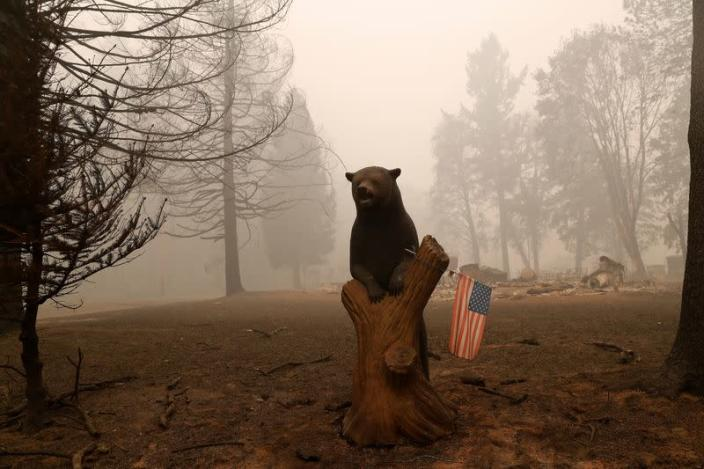 A U.S. flag is seen placed on a wooden bear outside a home that was destroyed in the aftermath of the Beachie Creek fire in Detroit, Oregon