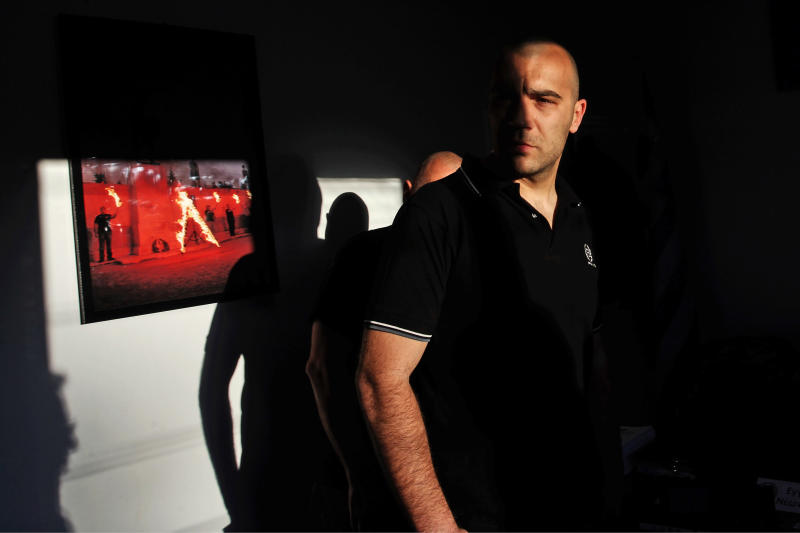In this Thursday, April 26, 2012 photo a member of far right wind Golden Dawn party stands in front of a photo of a party event at a memorial for the 480 B.C. Battle of Thermopylae at a party office in the suburban town of Artemis, 25 kilometers (15 miles) east of Athens. Reeling from a vicious financial crisis that has cost them pensions and jobs, Greeks have been turning away in droves from the mainstream politicians they feel have let them down. Firmly on the fringe of the right since it first appeared 20 years ago, Golden Dawn garnered a meager 0.23 percent in the 2009 elections. But its popularity has shot up over the past few months and support stood at about 5 percent in recent opinion polls, well above the 3 percent threshold needed to enter parliament. (AP Photo/Petros Giannakouris)