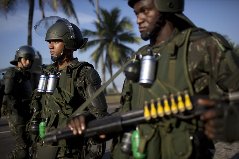 Brazilian Army soldiers in riot gear stand guard at the Barra da Tijuca beach before the auction of the Libra oil field, Brazil's largest single offshore find, in Rio de Janeiro, Brazil, Monday, Oct. 21, 2013. Monday's oil auction is the first in Brazil since the government created new production-sharing agreements. (AP Photo/Felipe Dana)