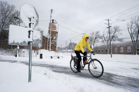 A bicyclist exits the Midtown Greenway bicycle and pedestrian trail during the spring snowstorm in Minneapolis, Minnesota, U.S., April 11, 2019. REUTERS/Annabelle Marcovici