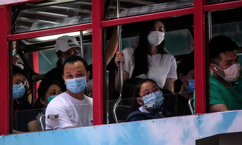Commuters wear face masks as they travel on a tram in Hong Kong
