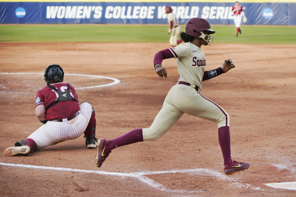 Florida State's Kalei Harding, right, scores behind Alabama catcher Bailey Hemphill, left, in the third inning of an NCAA Women's College World Series softball game Monday, June 7, 2021, in Oklahoma City. (AP Photo/Sue Ogrocki)