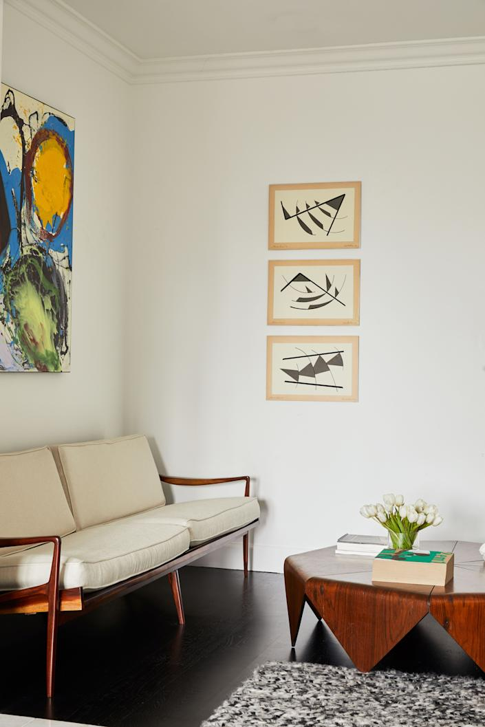 "<div class=""caption""> A corner of the master suite, furnished with a jacarandá loveseat produced in the 1950s by the Liceu de Artes e Ofícios in São Paulo. The coffee table, with wooden legs that fold down like origami, is one of Jorge Zalszupin's most recognizable pieces. The triptych by Geta Bratescu was shown at the 2017 Venice Biennale, in a pavilion dedicated to her 70-year career. </div>"