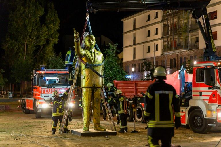 Firefighters use a crane to remove a four-metre golden statue of Turkish President Recep Tayyip Erdogan from a town square in the German city of Wiesbaden
