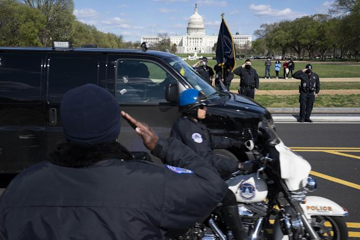 With the U.S. Capitol in the background, U.S. Capitol Police officers salute as procession goes by.