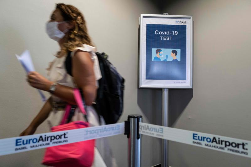 A passenger arriving from Istanbul and wearing a face mask, walks past a COVID-19 (novel coronavirus) test sign at the arrival hall of the Basel - Mulhouse Euroairport in Saint Louis, eastern France, on August 4, 2020. (Photo by SEBASTIEN BOZON / AFP) (Photo by SEBASTIEN BOZON/AFP via Getty Images)