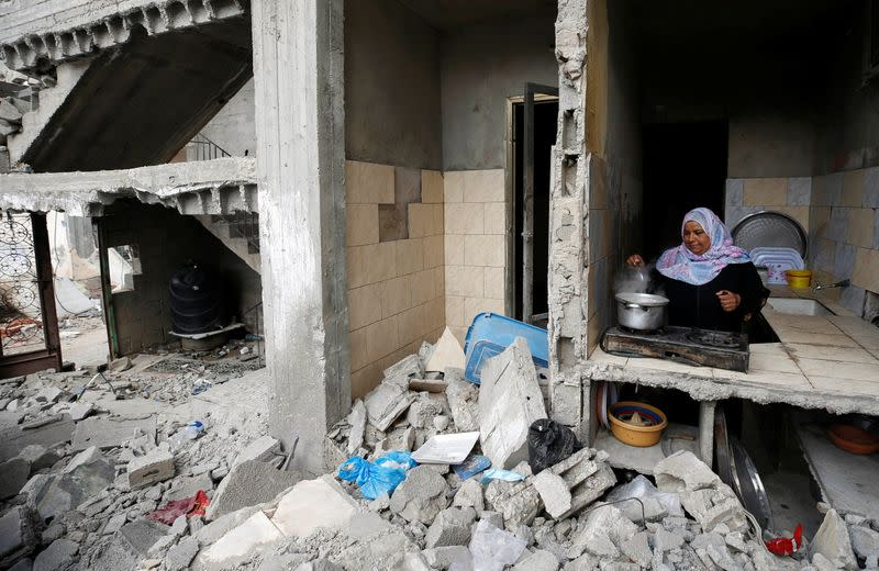 A Palestinian woman cooks amid the rubble of her house, which was destroyed by Israeli air strikes during the Israeli-Palestinian fighting, in Gaza