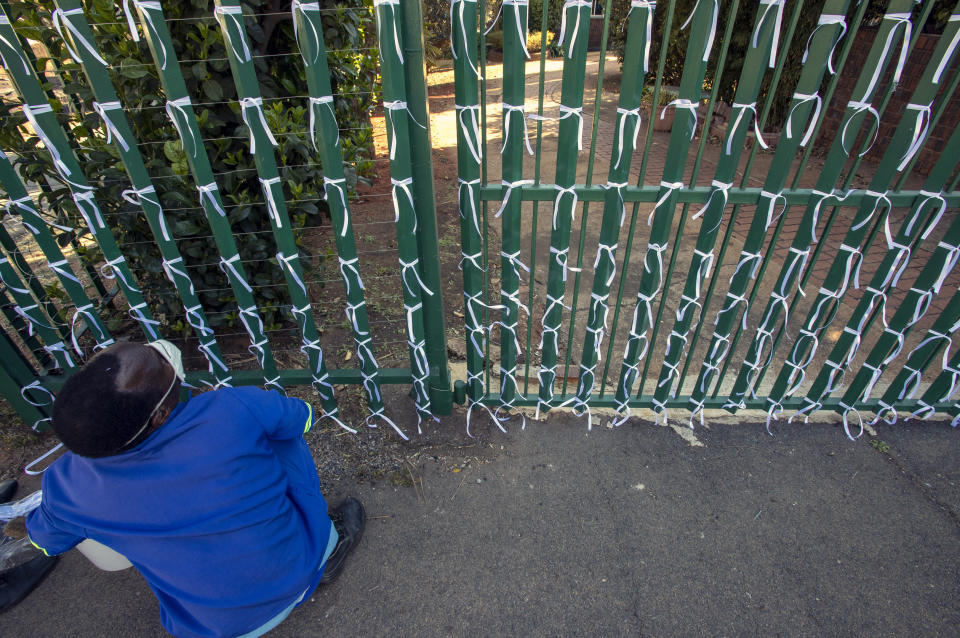 Silva Cossa, the caretaker, looks up as he ties ribbons onto the fence to represents a South African who has died from Covid-19, at St James Presbyterian church in Bedford Gardens, Johannesburg, South Africa, Wednesday, July 29, 2020. (AP Photo/Themba Hadebe)