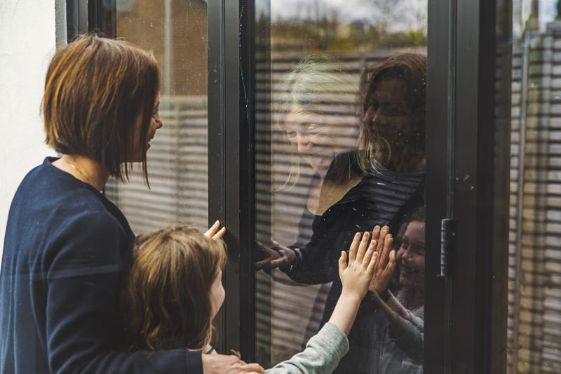 Senior lady is being shielded in the Covid-19 crisis. Her daughter and granddaughter visit her and speak to her through the window