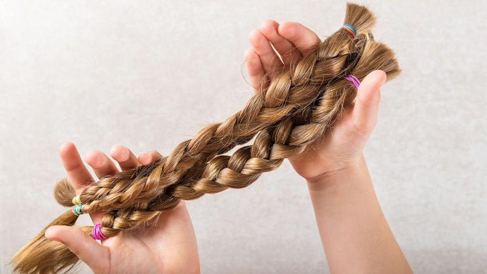holding long hair as donation for kids charity