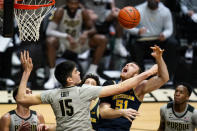 Purdue center Zach Edey (15) fouls Michigan forward Austin Davis (51) during the first half of an NCAA college basketball game in West Lafayette, Ind., Friday, Jan. 22, 2021. (AP Photo/Michael Conroy)