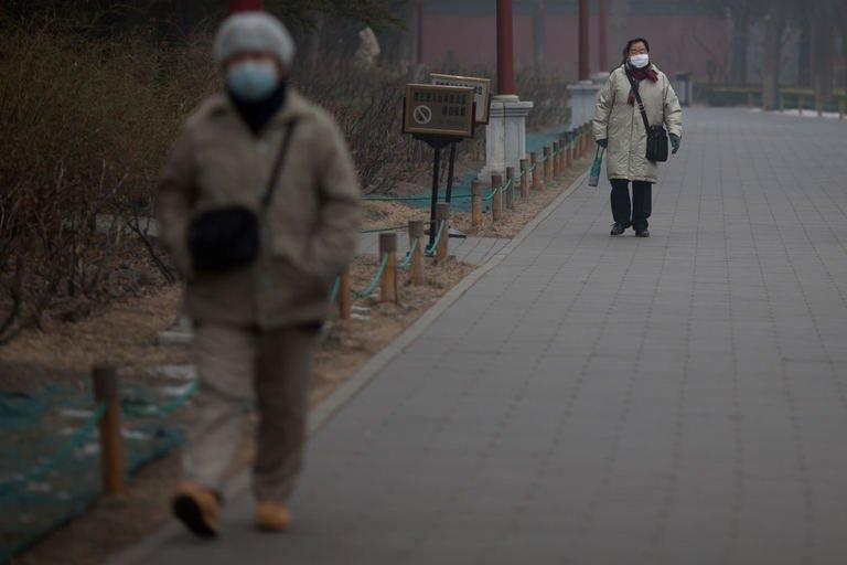 People wearing face masks walk through a park during heavily polluted weather in Beijing on January 30, 2013. Beijing authorities have stepped up their health warnings to residents as thick smog blanketed the Chinese capital and large swathes of the country for a third consecutive day