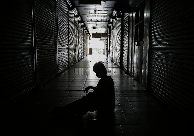 """A homeless person sleeps outside shops in the """"Roberto Huembes"""" market that are closed during a 24-hour nationwide general strike called by the opposition in Nicaragua (AFP Photo/INTI OCON)"""