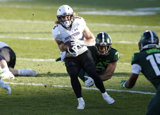 Northwestern's Drake Anderson (6) rushes against Michigan State's Xavier Henderson, rear, during the first half of an NCAA college football game, Saturday, Nov. 28, 2020, in East Lansing, Mich. (AP Photo/Al Goldis)