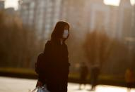 A woman wears a face mask outside an office complex in Beijing as the country is hit by an outbreak of the novel coronavirus