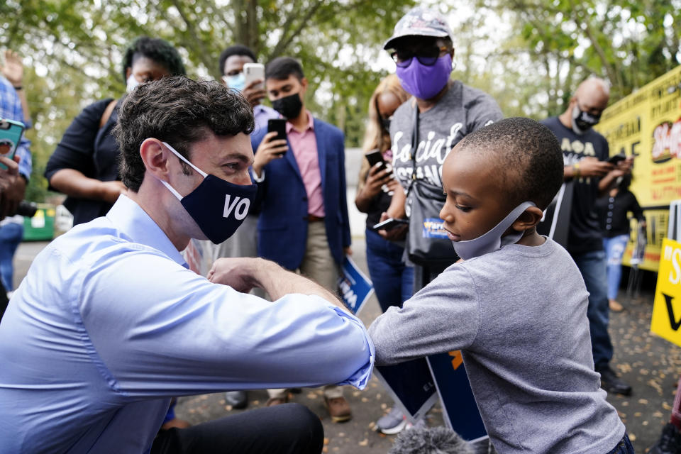 "Democratic candidate for Senate Jon Ossoff, left, greets Joshua Bias, 5, right, during a ""Get Out the Early Vote"" event at the SluttyVegan ATL restaurant on Tuesday, Oct. 27, 2020, in Jonesboro, Ga. (AP Photo/Brynn Anderson)"