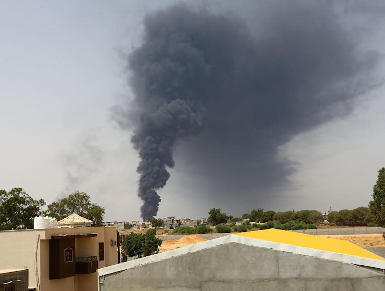 A picture taken on July 28, 2014 shows smoke billowing from an oil depot where a huge blaze started following clashes around Tripoli airport, in the south of the city (AFP Photo/Mahmud Turkia)
