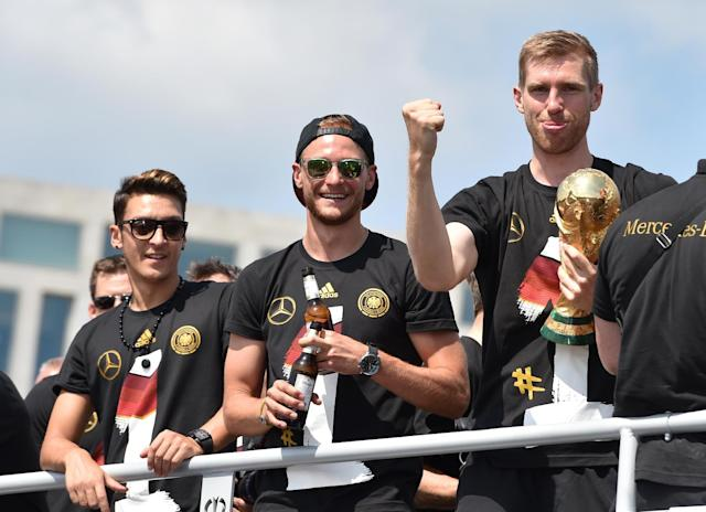"""German national soccer players, from left, Mesut zil, Benedikt Hoewedes and Per Mertesacker , celebrate as they tour Berlin by bus Tuesday July 15, 2014. Germany's World Cup-winning team has returned home from Brazil to celebrate the country's fourth title with huge crowds of fans. The team's Boeing 747 touched down at Berlin's Tegel airport midmorning Tuesday after flying a lap of honor over the """"fan mile"""" in front of the landmark Brandenburg Gate. (AP Photo/dpa, Jens Kalaene)"""