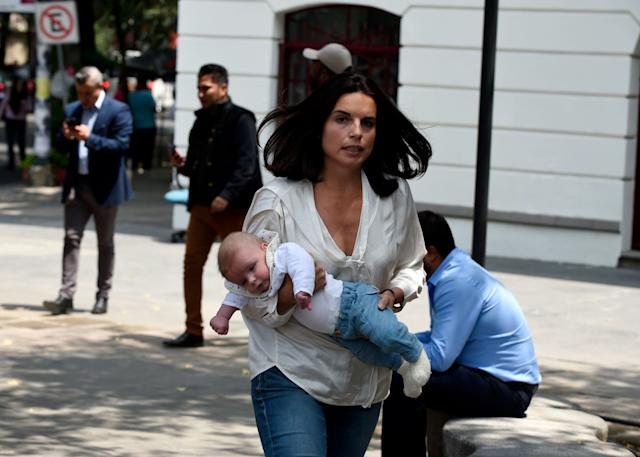 A woman carrying her baby rushes through the street.
