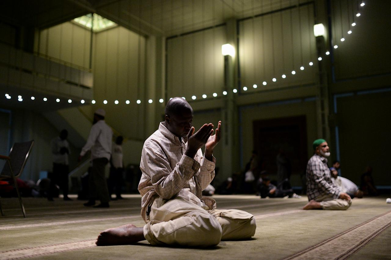 A Muslim American man holds up his hands in prayer after breaking fast and performing the Maghrib sunset prayer on the first day of Ramadan at the Islamic Cultural Center in Manhattan, New York, U.S., May 27, 2017.  REUTERS/Amr Alfiky        TPX IMAGES OF THE DAY