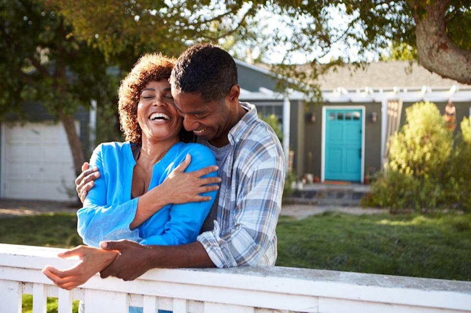 couple outdoors by house laughing, better wife after 40