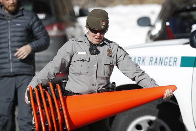 <p>Park Ranger Amy Fink carries cones to use in the Bear Lake trailhead in Rocky Mountain National Park, Saturday, Jan. 20, 2018, in Estes Park, Colo. Despite a government shutdown, Rocky Mountain National Park in Colorado and Yosemite National Park in California were open, but few Park Service staff were available to help visitors. (Photo: David Zalubowski/AP) </p>