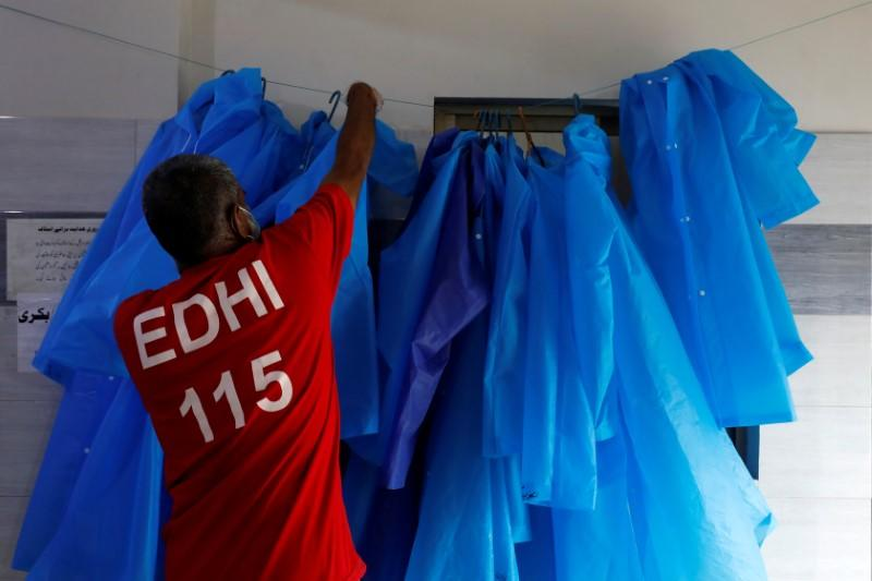 A volunteer of the Edhi Foundation, a non-profit social welfare programme, hangs up raincoats to be used to handle suspected carriers of the coronavirus disease (COVID-19), in Karachi, Pakistan