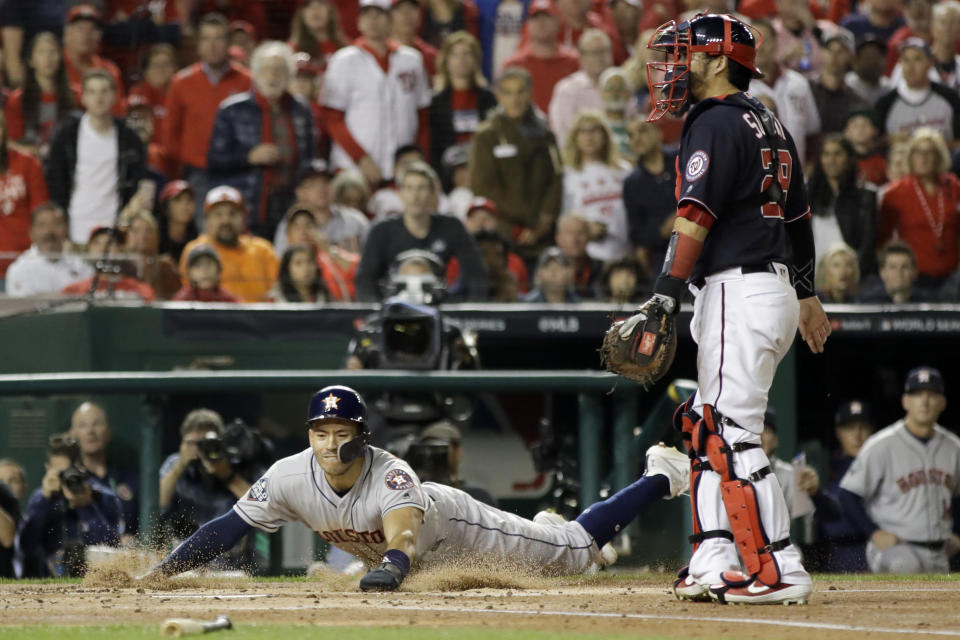 Houston Astros' Carlos Correa scores past Washington Nationals catcher Kurt Suzuki on a single by Josh Reddick during the second inning of Game 3 of the baseball World Series Friday, Oct. 25, 2019, in Washington. (AP Photo/Jeff Roberson)