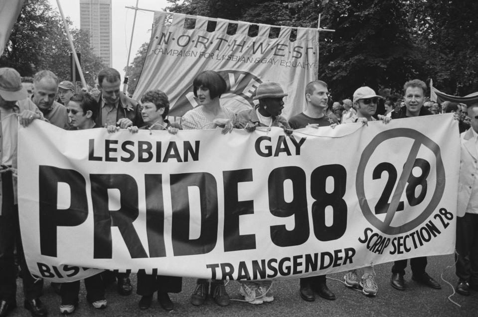 Celebrities help to hold a banner opposing Section 28, at the Lesbian, Gay, Bisexual, and Transgender Pride event, London, 4th July 1998. Those present include (from second left) actor Michael Cashman, comedian Rhona Cameron and activist Peter Tatchell. First and second from right are musician and radio presenter Tom Robinson, and comedian and TV presenter Graham Norton. (Steve Eason/Hulton Archive/Getty Images)