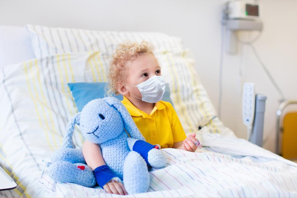 Little boy playing wearing face mask with his toy in bed in hospital room. Child with IV tube and pulse oximeter in clinic. Kid recovering from coronavirus. Corona virus outbreak. Patient in kids ward