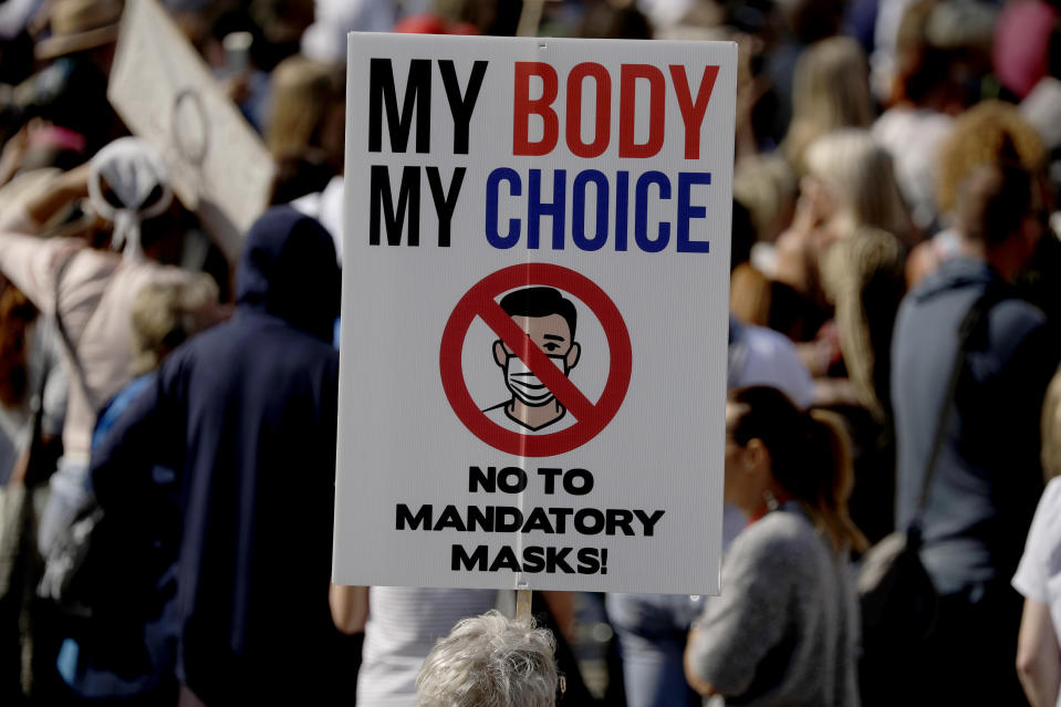 """A protester holds up a placard as they take part in a """"Resist and Act for Freedom"""" protest against a mandatory coronavirus vaccine, wearing masks, social distancing and a second lockdown, in Trafalgar Square, London, Saturday, Sept. 19, 2020. (AP Photo/Matt Dunham)"""