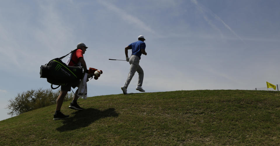 Tiger Woods, right, climbs to the first green after hitting a shot during round-robin play at the Dell Match Play Championship golf tournament, Wednesday, March 27, 2019, in Austin, Texas. (AP Photo/Eric Gay)