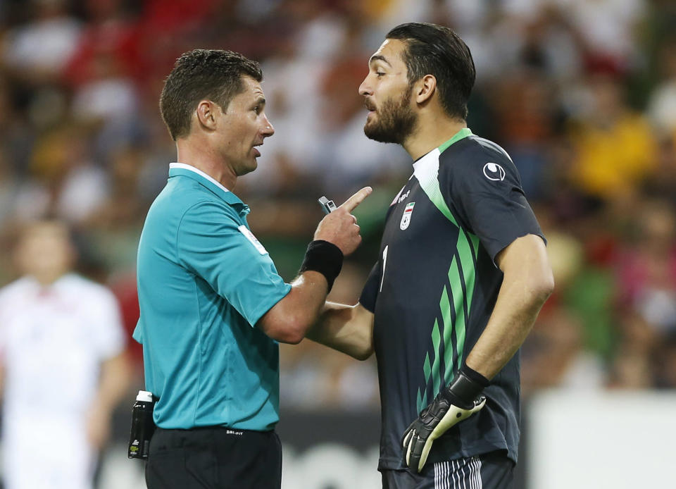 Referee Benjamin Williams of Australia speaks to Iran's goalkeeper Alireza Haghighi (R) following his collision with Bahrain's Faouzi Aaish (not pictured) in the Iranian penalty box during their Asian Cup Group C soccer match at the Rectangular stadium in Melbourne January 11, 2015. REUTERS/Brandon Malone (AUSTRALIA - Tags: SOCCER SPORT)