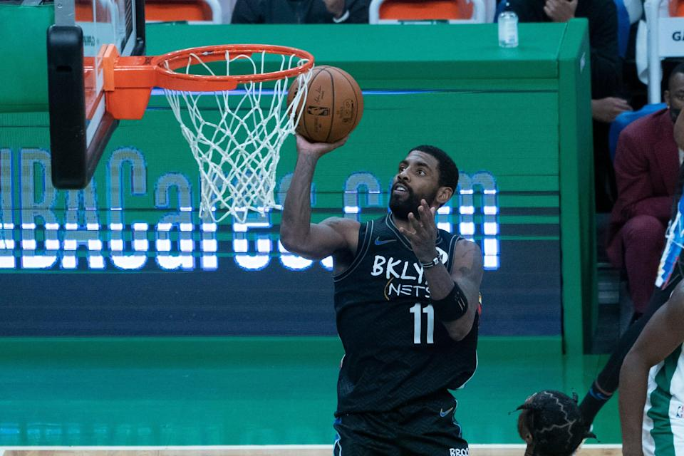 Brooklyn Nets point guard Kyrie Irving (11) shoots a layup during the fourth quarter against the Boston Celtics at TD Garden on Christmas Day of 2020.