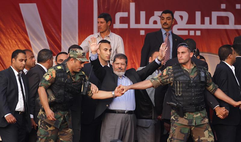 FILE - In this June 29, 2012 file photo, Egypt's President-elect Mohammed Morsi waves to supporters after giving a speech at Tahrir Square in Cairo. It was one of the most perplexing events of Egypt's 2011 revolution: Attacks on prisons that broke out more than 20,000 inmates, among them Hamas and Hezbollah militants and Muslim Brotherhood leaders, including the man who is now the country's president, Mohammed Morsi. Now a court case is trying to uncover for the first time who was behind the attacks, raising political headaches for Morsi. (AP Photo/Khalil Hamra, File)