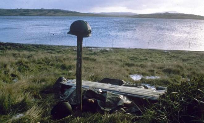 Steel helmets mark a makeshift grave for Argentines killed in the Falklands War.