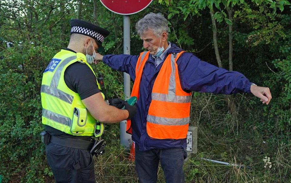 A police officer searches a protester at a slip road at junction 18 of the M25, near Rickmansworth (PA Wire)