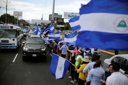 People hold Nicaraguan flags while forming a human chain to demand justice for people who died during anti-government protests, in Managua
