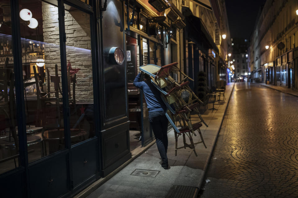 A waiter closes a bar terrace in Paris, Saturday, Oct. 17, 2020. French restaurants, cinemas and theaters are trying to figure out how to survive a new curfew aimed at stemming the flow of record new coronavirus infections. The monthlong curfew came into effect Friday at midnight, and France is deploying 12,000 extra police to enforce it. (AP Photo/Lewis Joly)
