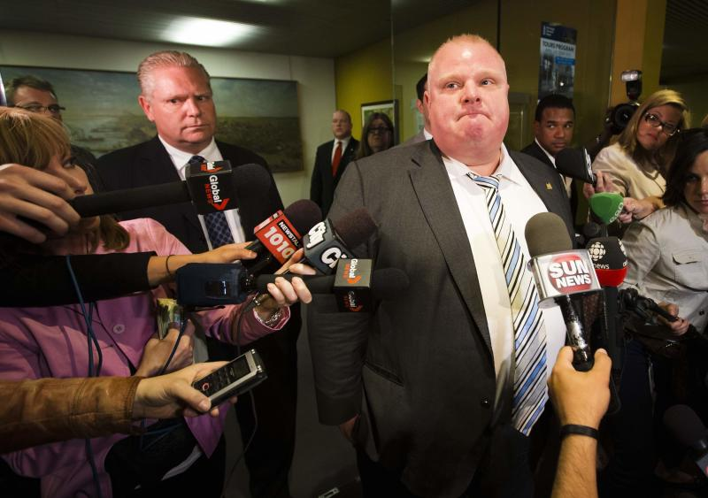 Toronto Mayor Rob Ford makes a statement to the media at City Hall alongside his brother and city councillor Doug Ford (L), after his press secretary George Christopoulos and deputy press secretary Isaac Ransom resigned in Toronto in this May 27, 2013 file photo. Toronto Mayor Rob Ford's brother will run for election in his place after the mayor withdrew from the race on September 12, 2014 due to a health crisis. REUTERS/Mark Blinch/Files (CANADA - Tags: POLITICS)