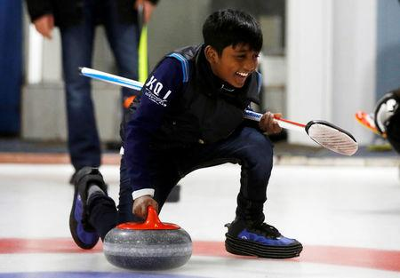 """A refugee from Sri Lanka, Arun Daniel, learns the sport of curling at the Royal Canadian Curling Club during an event put on by the """"Together Project"""", in Toronto, March 15, 2017.    REUTERS/Mark Blinch"""