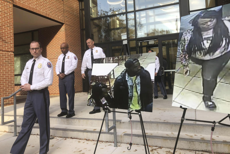Prince George's County Police Chief Hank Stawinski addresses reporters outside a police station in Upper Marlboro, Md., Tuesday, Nov. 5, 2019, standing next to a photo of a man police suspected of killing a man and a photo of a woman who was apparently with the suspect. Police are trying to identify the suspect accused of fatally stabbing a man who was cutting in line for a chicken sandwich at a Popeyes restaurant in Maryland. (AP Photo/Michael Kunzelman)