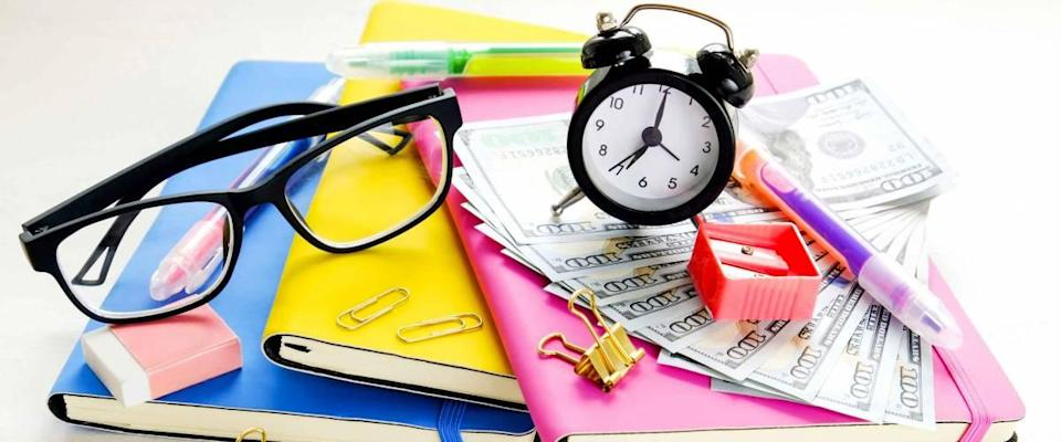 Investing time & money in expensive education, college tuition & fees concept. Pack of new one hundred dollar bills, notebooks, school supplies, alarm clock.