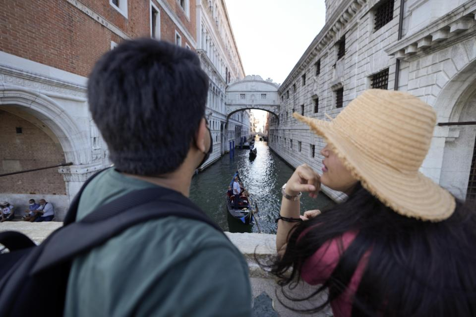 A couple admires the Ponte dei Sospiri (Bridge of Sighs), in Venice, Italy, Thursday, June 17, 2021. After a 15-month pause in mass international travel, Venetians are contemplating how to welcome visitors back to the picture-postcard canals and Byzantine backdrops without suffering the indignities of crowds clogging its narrow alleyways, day-trippers perched on stoops to imbibe a panino and hordes of selfie-takers straining for a spot on the Rialto Bridge or in front of St. Mark's Basilica. (AP Photo/Luca Bruno)