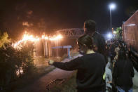 People look at flames engulfing the Industry Bridge in Rome, early Sunday, Oct. 3, 2021. A blaze, possibly sparked by a gas canister explosion, destroyed part of an historic bridge spanning the Tiber River in Rome before firefighters extinguished the flames early Sunday. (Mauro Scrobogna/LaPresse via AP)