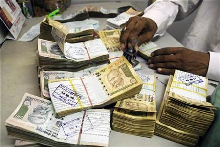 An employee arranges Indian currency notes at cash counter inside a bank in Agartala