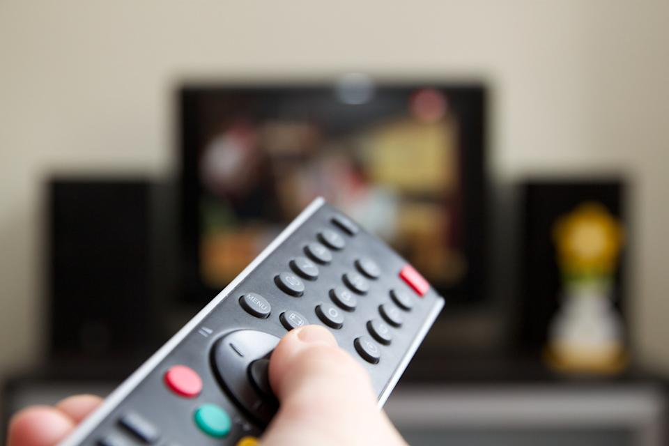 Human hand holding remote control changing Channels with television set.