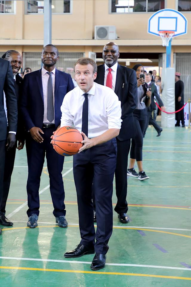French President Emmanuel Macron prepares to shoot the ball during a meeting with former pro basketball players from NBA Africa and takes part in a practice session with young basketball players in the French Louis Pasteur high school in Lagos, Nigeria, July 4, 2018. Ludovic Marin/Pool via Reuters