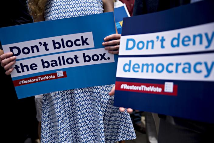 """An attendee holds a """"Don't block the ballot box"""" sign during a news conference on the state of voting rights in the United States in Washington in June of 2019. (Photo: Andrew Harrer/Bloomberg/Getty Images)"""