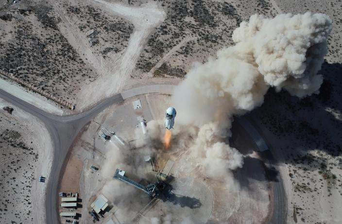 In this Jan. 14, 2021 photo made available by Blue Origin, the New Shepard NS-14 rocket lifts off from Launch Site One in West Texas. On Tuesday, July 20, 2021, Blue Origin's 60-foot (18-meter) New Shepard rocket will accelerate toward space at three times the speed of sound, or Mach 3, before separating from the capsule and returning for an upright landing. (Blue Origin via AP)